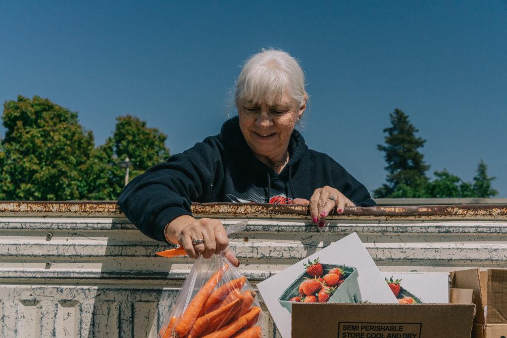 Elderly Woman Distributing Carrots